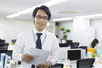 資料を手に微笑むビジネス男性 33000000885| 写真素材・ストックフォト・画像・イラスト素材|アマナイメージズ