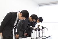 謝罪会見で頭を下げるビジネス男性3人