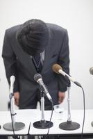 謝罪会見で頭を下げるビジネス男性