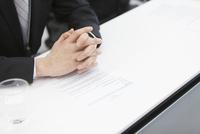 書類の上で組まれたビジネス男性の手