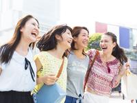 街で肩を合わせて歩く4人の女性