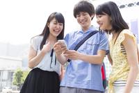 街中でスマートフォンを見て微笑む3人の若者