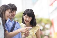 街中でスマートフォンを見て微笑む3人の若者 33000000959| 写真素材・ストックフォト・画像・イラスト素材|アマナイメージズ