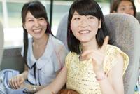 バスの車中でイヤホンをして景色を見る2人の女性