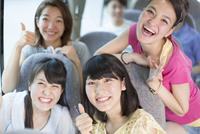 バスの中で笑う4人の車中のスナップ 33000000976| 写真素材・ストックフォト・画像・イラスト素材|アマナイメージズ
