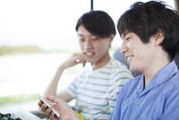 バスの中でスマートフォンを見る2人の男性