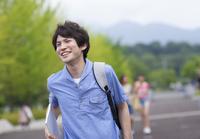微笑みながらキャンパスを歩く男子学生 33000001021| 写真素材・ストックフォト・画像・イラスト素材|アマナイメージズ