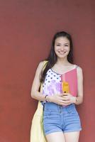 赤い壁の前で微笑む女子学生のポートレート