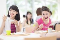 学食で食べるポーズをする2人の女子学生