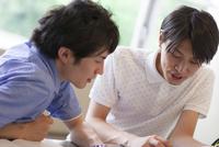ペンを持って会話する2人の男子学生