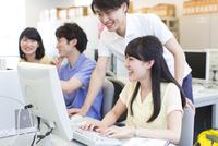 パソコン教室で会話をする学生たち
