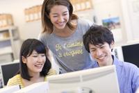 パソコン教室でモニターに向かう3人の学生