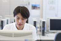 パソコン教室でモニターに向かう男子学生
