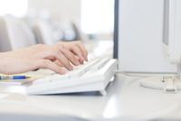 パソコンのキーボードを打つ女性の手