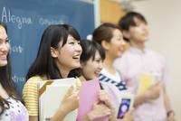 黒板の前に笑顔で並ぶ学生たち