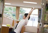 図書室で勉強中に伸びをする男子学生