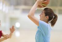 バスケットでシュートをする若い女性