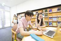 ノートパソコンを見る学生男女