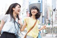 笑顔で街を歩く2人の若い女性