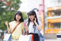 スマートフォンを持って歩く買物中の若い女性2人