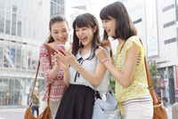 スマートフォンを見つめて喜ぶ3人の若い女性