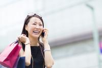 スマートフォンで会話する買物中の女性