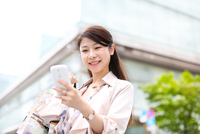 スマートフォンを見る買物中の女性