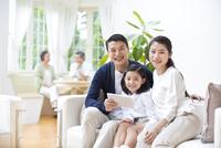 会話する祖父母とソファに掛けて笑顔の親子