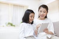 タブレットPCを見る母と娘