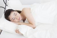ベットで横向きに眠る女性