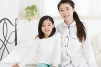 ベットに掛けて笑う母と娘