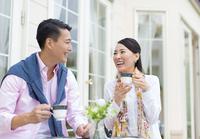 コーヒーカップを手に笑い合うカップル