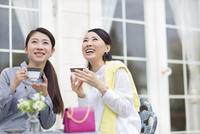 コーヒーカップを手に見上げる2人の女性 33000001471| 写真素材・ストックフォト・画像・イラスト素材|アマナイメージズ