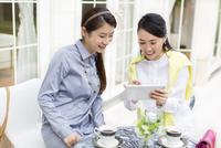 カフェのテーブルでタブレットPCを見る2人の女性 33000001474| 写真素材・ストックフォト・画像・イラスト素材|アマナイメージズ
