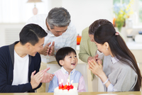 ケーキを前に誕生日のお祝いをする家族