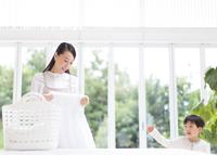洗濯物を見る奥さんと男の子 33000001533| 写真素材・ストックフォト・画像・イラスト素材|アマナイメージズ