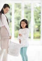 洗濯カゴを持って微笑む母と娘 33000001534| 写真素材・ストックフォト・画像・イラスト素材|アマナイメージズ