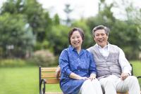 ベンチに掛けて笑うシニア夫婦