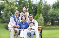 ベンチに揃って笑顔の三世代家族