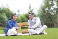 芝に腰かけて会話するシニア夫婦