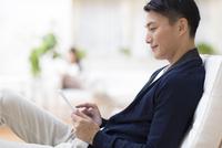 リラックスチェアに座りタブレットPCを見る男性