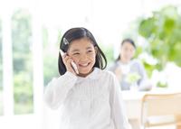 スマートフォンで会話する女の子 33000001584| 写真素材・ストックフォト・画像・イラスト素材|アマナイメージズ