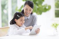 母の持つタブレットPCにタップする女の子 33000001586| 写真素材・ストックフォト・画像・イラスト素材|アマナイメージズ
