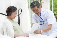 ベットのシニア女性にタブレットPCで説明する医者