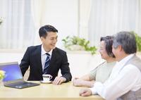 説明する訪問営業の男性と話を聞くシニア夫婦