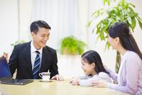 説明する訪問営業の男性と話を聞く母と娘