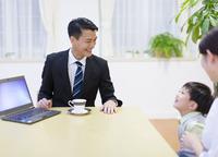 訪問営業の男性と会話する母と男の子