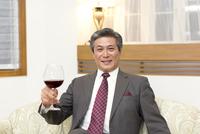 ワイングラスを手にポーズをとるシニア男性