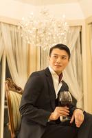 ワイングラスを手にポーズをとる若い男性