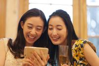 スマートフォンで楽しむ2人の女性